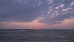 Kiter in shallow water performs tricks against the sunset. A man in a suit for diving, performs stunts on kitesurf stock video footage