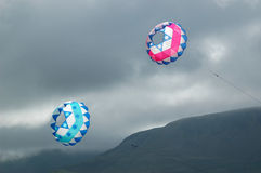 Kites flying in stormy sky. Two colorful, pink and blue kites flying in a rainy, stormy sky Royalty Free Stock Photos