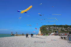 Kites on a pebbles beach. Launching kites on a sunny and windy day on a pebbles beach in Fecamp Normandy France royalty free stock photo