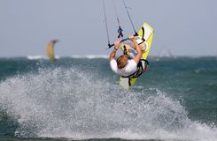 Kitesurf Backroll. Kitesurfer jumps and spins under the kite with a huge spray of water Stock Images