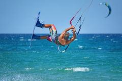 Kitesurfer выполняя kiteboarding фокусы - весьма водные виды спорта Стоковые Изображения