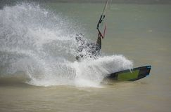 Kitesurfer in action on tropical sea. Recreational sport kitesurfer surfing over lagoon in tropcial sea with wake splash Royalty Free Stock Images