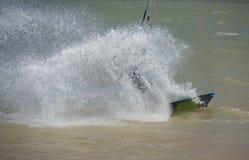 Kitesurfer in action on tropical sea. Recreational sport kitesurfer surfing over lagoon in tropcial sea with wake splash Stock Photo
