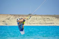 Kiteboarder performing kiteboarding jumps and tricks. Kitesurfer athlete performing kitesurfing jumping tricks. Spectacular jumps with the kite while kiting royalty free stock photography