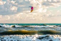 Kitesurfer berijdt vlieger door het surfen golven van het stormachtige breken van de Zwarte Zee op zandige kust Stock Afbeelding