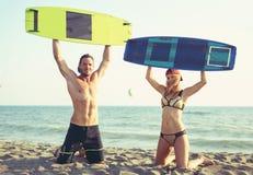Kitesurfer caucasien de femme appréciant l'été sur la plage sablonneuse avec son ami Photos libres de droits
