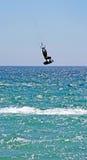 Kitesurfer, das hoch durch die Luft als sein Drachen fliegt, schlägt etwas ernsten Wind. Stockfotografie