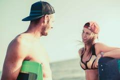 Kitesurfer de femme appréciant l'été sur la plage sablonneuse avec son ami Photographie stock libre de droits