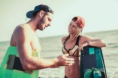 Kitesurfer de femme appréciant l'été sur la plage sablonneuse avec son ami Image stock