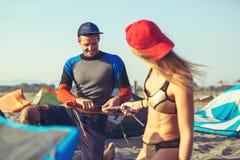 Kitesurfer de femme appréciant l'été sur la plage sablonneuse avec son ami Images libres de droits