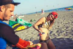 Kitesurfer de femme appréciant l'été sur la plage sablonneuse avec son ami Photos stock