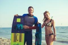 Kitesurfer de femme appréciant l'été sur la plage sablonneuse avec son ami Images stock