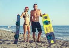 Kitesurfer de femme appréciant l'été sur la plage sablonneuse avec son ami Photo libre de droits