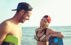 Kitesurfer de femme appréciant l'été sur la plage sablonneuse avec son ami Image libre de droits