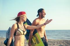 Kitesurfer de femme appréciant l'été sur la plage sablonneuse avec son ami Photographie stock
