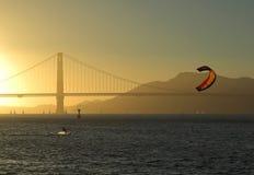 Kitesurfer delante del puente de puerta de oro, puesta del sol de San Francisco Foto de archivo