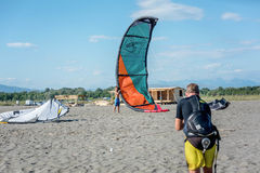 Kitesurfer die zijn machtsvlieger in de lucht op het strand proberen op te heffen Royalty-vrije Stock Foto