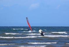 Kitesurfer e windsurfer no mar imagem de stock