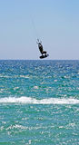 Kitesurfer flying high through the air as his kite hits some serious wind. Extreme sports with kitesurfer enjoying vacation, flying high through the air over stock photography
