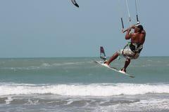 Kitesurfer gumping boven het water Stock Afbeelding