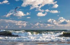 Kitesurfer jedzie jego kanię przez fala burzowy morze krajobraz Zdjęcia Royalty Free
