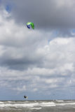 Kitesurfer jumping into the air. Kitesurfer increasing speed and jumping into the air Royalty Free Stock Photo