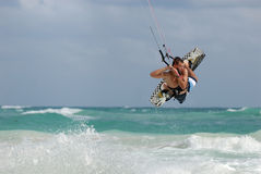 Kitesurfer jumping waves. Kitesurfer jumping wave in idyllic caribbean sea Royalty Free Stock Images