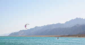 Kitesurfer in lagoon. Surrounded by desert mountains Royalty Free Stock Images