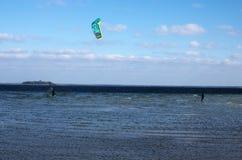 Kitesurfer och surfare som får klara för att åka skridskor på vågorna Fotografering för Bildbyråer