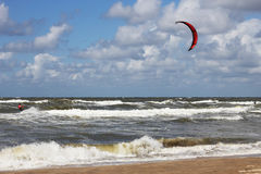 Kitesurfer passing by in the surf. Kitesurfer close to the beach Royalty Free Stock Photography