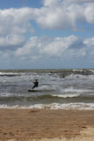 Kitesurfer passing by in the surf. Kitesurfer close to the beach Stock Image