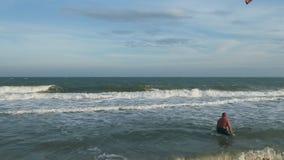 Kitesurfer rende il salto di vibrazione al disopra della superficie dell'oceano video d archivio