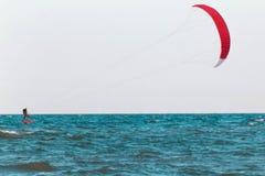 Kitesurfer rider i det öppna havet som är osean med rött, seglar Arkivfoton