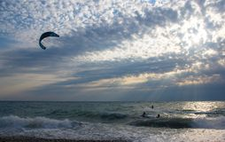 kitesurfer rides a kite-surf on waves of the sea royalty free stock images
