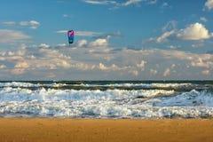 Kitesurfer rides kite through surfing waves of stormy sea at sandy beach at sunset by Anapa. Anapa, Russia - July 19, 2016: Kitesurfer rides kite through surfing royalty free stock image