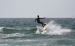 Kitesurfer with a sail boat Stock Images