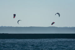 Kitesurfer sails above a pier Stock Images