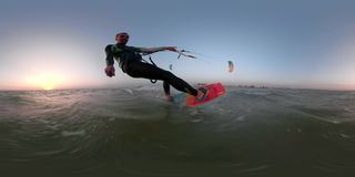 A man in a suit for diving deals with kitesurfing at dawn, 360 degrees. Kitesurfer at sea, riding at sunrise with self stick stock footage