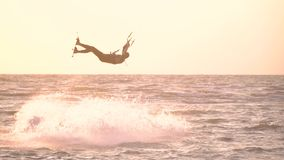 A man does a somersault in the air and falls into the water. Kitesurfer in a suit for diving does the trick in the air and falls into the water stock footage