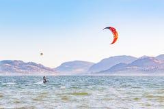 Kitesurfer sur le lac avec le ciel bleu et les montagnes à l'arrière-plan Photo libre de droits
