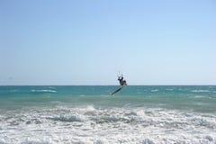 Kite surfer performing tricks. Kite surfer performing aerial tricks on waves against blue skies royalty free stock photo