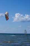 Kitesurfer and windsurfer in action. Royalty Free Stock Photo