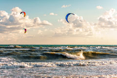 Kitesurfers乘驾风筝通过风雨如磐的海冲浪的波浪Blaga海滩胜地的在日落 免版税库存照片