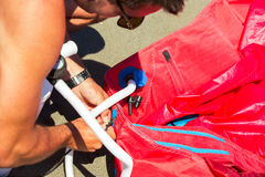 Kitesurfers on the beach prepare sport equipment for riding Royalty Free Stock Photography