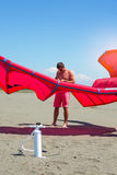 Kitesurfers on the beach prepare sport equipment for riding Stock Photo