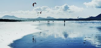 Kitesurfers at Famara Beach in Lanzarote, Spain. A panoramic view of the Famara Beach in Lanzarote, Canary Islands, Spain, with some unrecognizable swimmers and Royalty Free Stock Photography