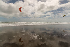 Kitesurfers on Muriwai beach Royalty Free Stock Images