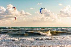 Kitesurfers ride kites through surfing waves of stormy sea at Blaga Beach resort at sunset. Anapa, Russia - July 19, 2016: Kitesurfers ride kites through surfing royalty free stock photos