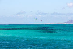 Kitesurfers surfing on a flat azure water of Atlantic ocean in Corralejo. Fuertevetnura Royalty Free Stock Photography