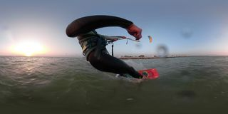 A man on a kitesurf ride on the sea, shooting 360 degrees. Kitesurfing at dawn, a man in a diving suit manages a training kite on a bright wakeboard stock video